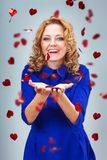 Blonde woman catching heart shapes Royalty Free Stock Photography