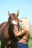 Blonde woman and chestnut horse Royalty Free Stock Photos