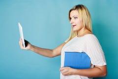 Blonde woman choosing between book and tablet Stock Image