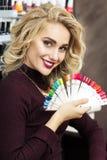 Blonde woman choosing nail polish color stock image
