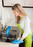 Blonde woman cleaning pipe with cup plunger Stock Photos
