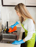Blonde woman cleaning pipe with detergent Royalty Free Stock Images
