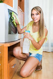 Blonde woman cleaning TV at home Stock Image