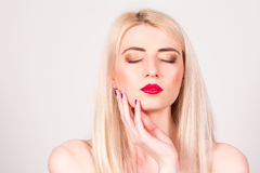 Blonde woman with closed eyes and with a manicure in the studio. Manicure. Stock Image
