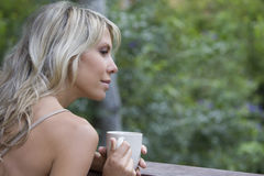 Blonde Woman With Coffee Cup Against Blurred Plants Royalty Free Stock Photography