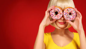 Blonde woman with colorful donuts over red Stock Photo