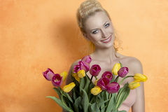 Blonde woman with colourful bouquet Royalty Free Stock Images