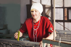 Blonde woman with comb at the factory Stock Images