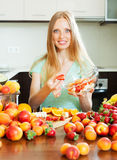 Blonde woman cooking fruit salad Royalty Free Stock Photography