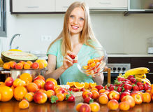 Blonde woman cooking fruit salad Stock Image