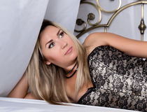 Blonde woman in a corset and denim lying in bed in bright room. Fashion portrait of model indoors Royalty Free Stock Image