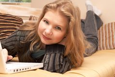 Blonde woman on the couch. Blonde woman in casual clothes lying on the couch and working on her laptop Royalty Free Stock Photos