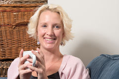 Blonde Woman on Couch with Hot Drink Smiles COPY SPACE Stock Images