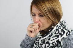 Blonde woman coughing. Young woman coughing over a white background Stock Photography