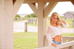Blonde woman on country porch royalty free stock photos