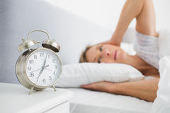 Blonde woman covering her ears from alarm clock noise in bed. At home in bedroom royalty free stock image