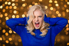 Blonde woman covering her ears and screaming Stock Photos
