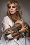 Blonde woman with crocodile in hands Stock Photography