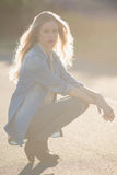 Blonde woman crouching down on a highway. Looking at camera Royalty Free Stock Photos