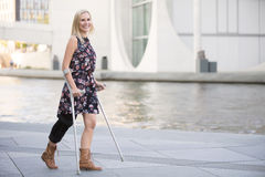Blonde woman with crutches. Blonde woman in a dress walking with crutches Stock Image