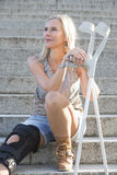 Blonde woman with crutches Royalty Free Stock Photo
