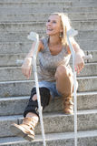 Blonde woman with crutches Stock Image