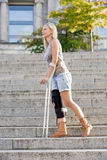 Blonde woman with crutches Stock Images