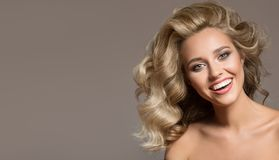 Blonde woman with curly beautiful hair smiling. On gray background royalty free stock photos