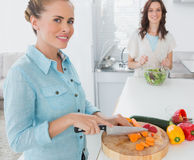 Blonde woman cutting carrots with her friend tossing salad Stock Photos