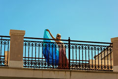 Blonde woman dancing on balcony. Seen from below, an attractive blonde woman wearing a long dress and holding a blue veil is dancing across an outside baclony Royalty Free Stock Photo