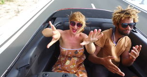 Blonde woman dancing with black friend in the back seat of convertible. Beautiful blonde woman and handsome african american man riding in the back seat of stock footage