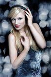 Blonde woman dancing with headphones. On silver background stock photo