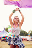 Blonde woman dancing with hula hoop at a music festival, vertical Stock Image