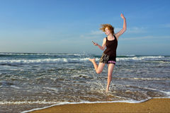 Blonde woman dancing with mobile phone on beach Stock Images