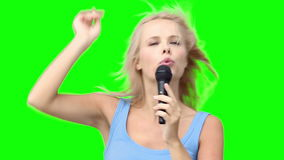 Blonde woman dancing while singing into a microphone stock video footage