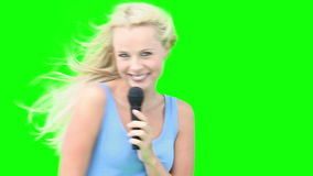 Blonde woman dancing while singing with a microphone stock video