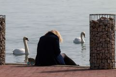 Blonde woman in a dark coat is sitting at the lakeside on the coast. The blonde woman in the dark blue coat  is bending forward towards the lake deep in thought Stock Images