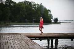 Blonde woman on the deck at lake Stock Photo