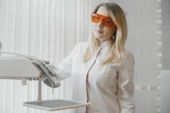 Blonde woman dentist standing next to dental equipment in stomatology. Blonde woman dentist in white uniform standing next to dental equipment in bright royalty free stock images