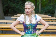 Blonde woman in dirndl. In beer garden stock photography