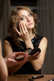 Blonde woman doing evening make-up before mirror Royalty Free Stock Image