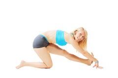 Blonde woman doing gymnastics in a kneeling pose Royalty Free Stock Photography