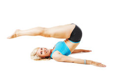 Blonde woman doing gymnastics lying on her back Stock Image