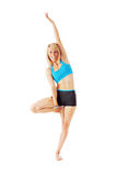 Blonde woman doing gymnastics by standing on one foot Royalty Free Stock Photos