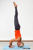 Blonde woman doing handstand on the mat indoors Royalty Free Stock Photos