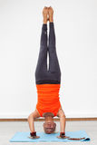 Blonde woman doing handstand on the mat Royalty Free Stock Photography