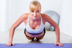 Blonde woman doing push-ups Stock Photos