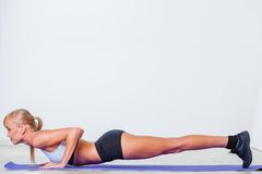 Blonde woman doing push-ups Stock Image
