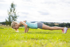 Blonde woman doing push-ups outdoor in the park Royalty Free Stock Photos