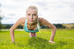 Blonde woman doing push-ups in the park Stock Image